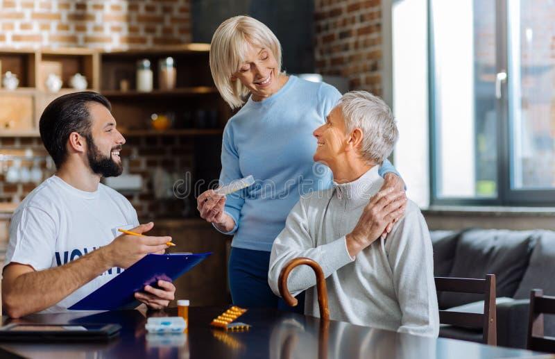 Épouse affectueuse aimable approchant son mari âgé et son assistant social photographie stock libre de droits