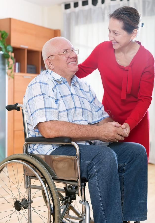 Épouse aimante à côté de son mari dans le fauteuil roulant photo stock