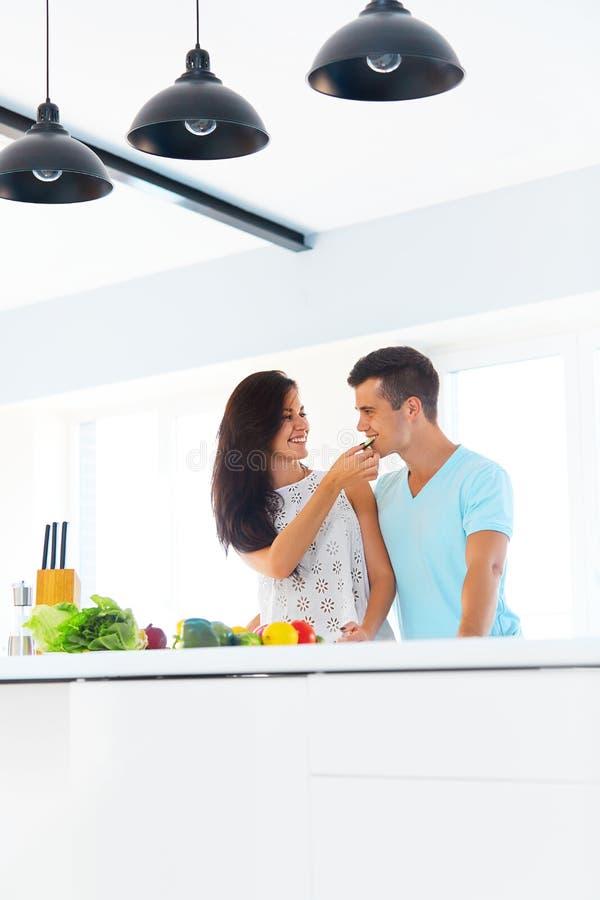 Épouse alimentant son mari dans leur cuisine photographie stock libre de droits