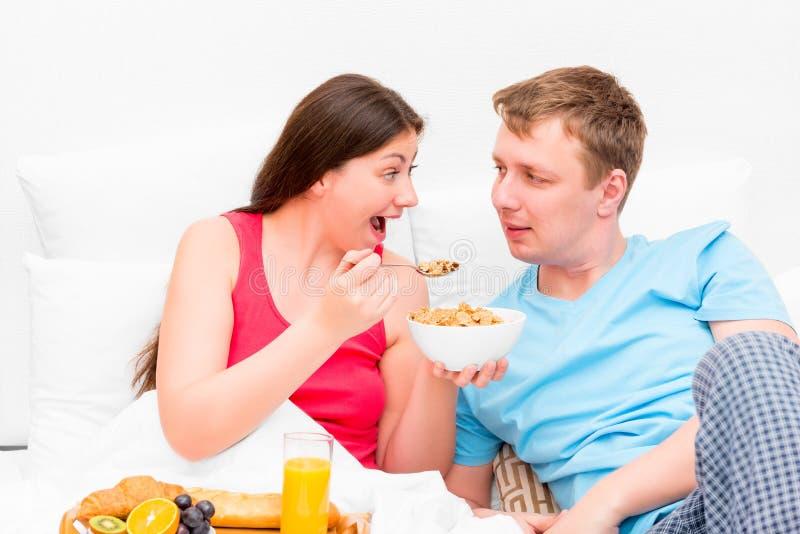 Épouse alimentant son petit déjeuner de mari images stock