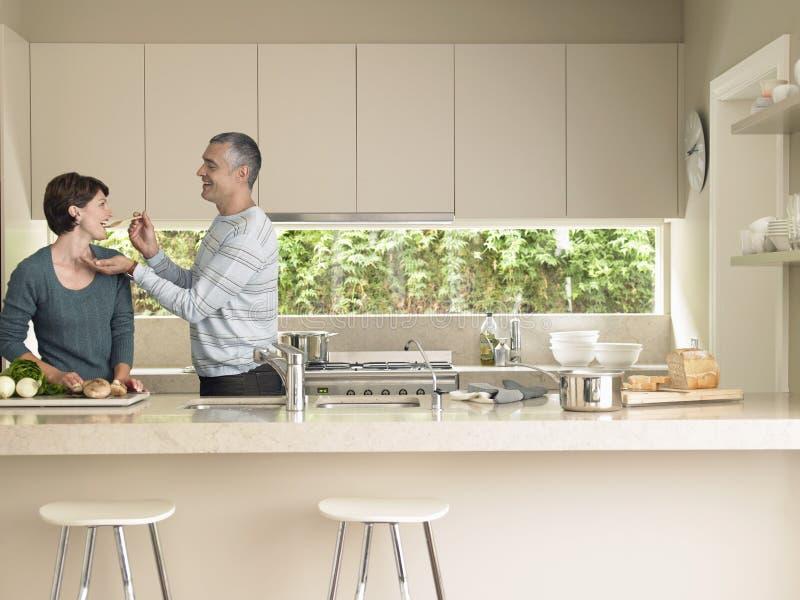 Épouse de alimentation d'homme au comptoir de cuisine photographie stock