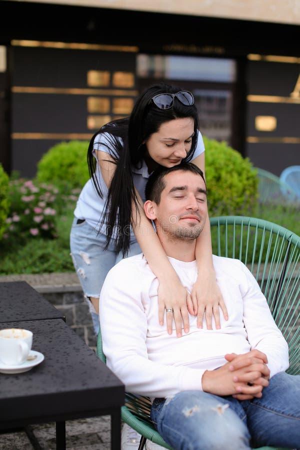 Épouse embrassant le mari s'asseyant dans la chaise au café de rue dehors photos libres de droits