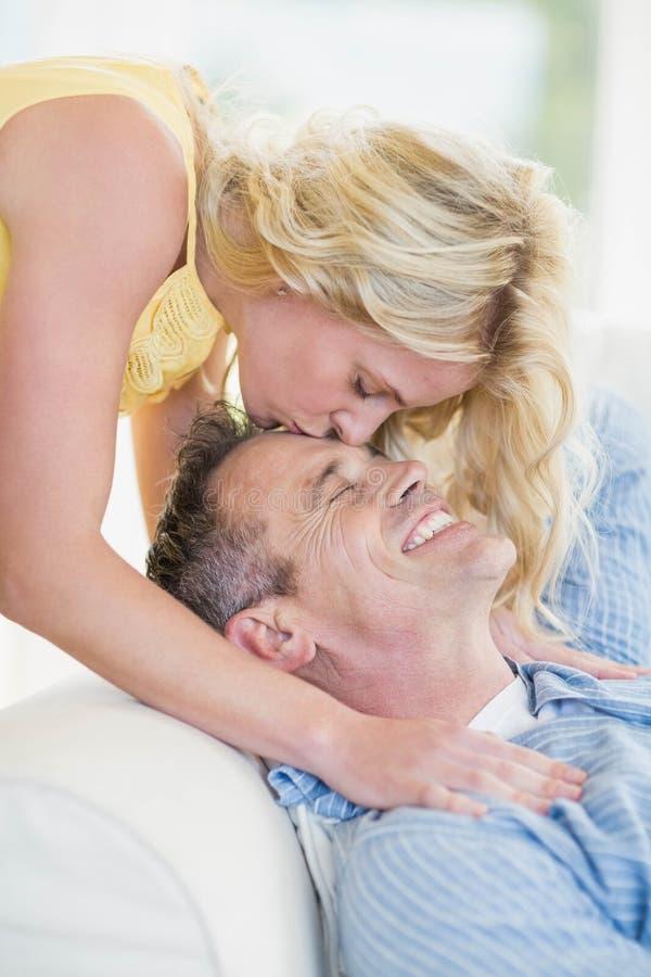 Épouse embrassant le mari sur le front photos stock