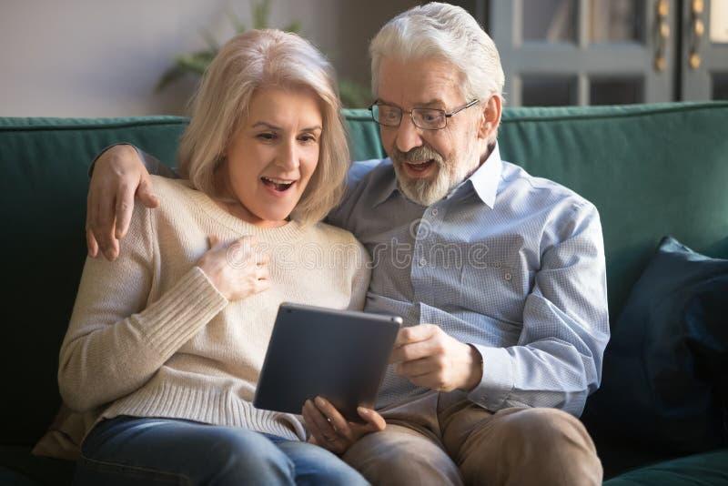 Épouse et mari mûrs étonnés à l'aide du comprimé, lisant des nouvelles agréables images libres de droits