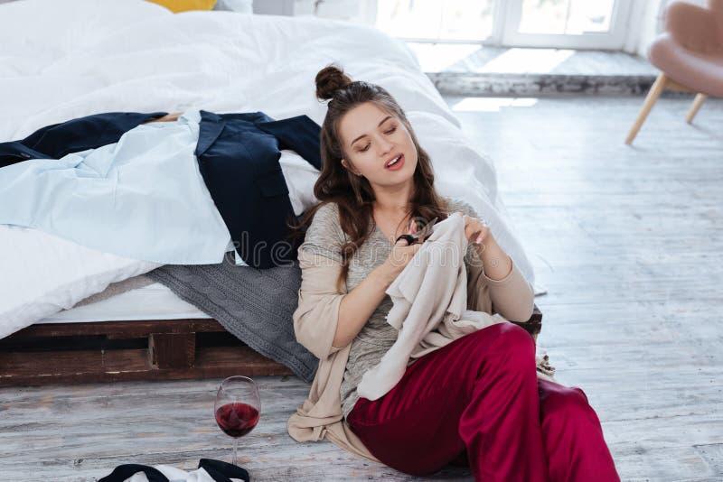Épouse ex s'asseyant sur le plancher près du lit avec des ciseaux photographie stock