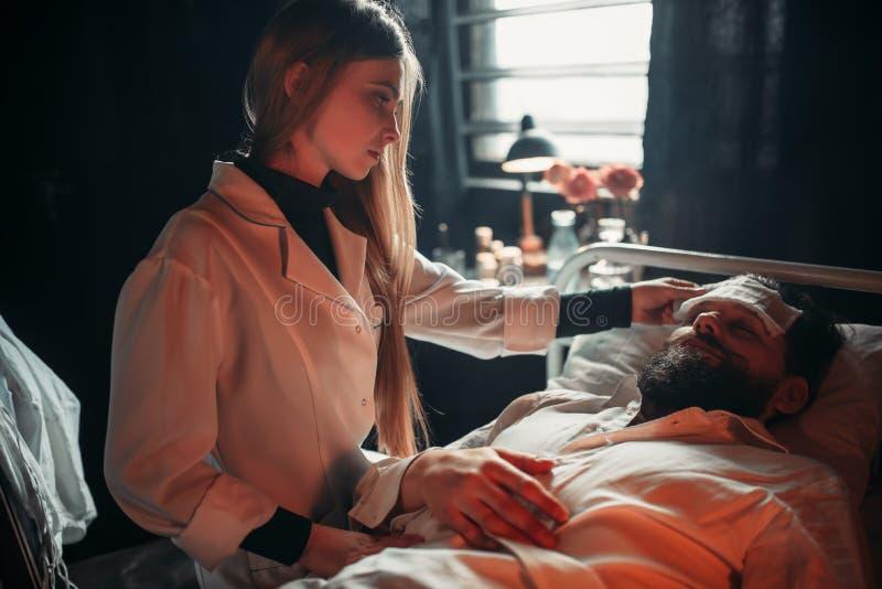Épouse s'asseyant contre le mari malade dans le lit d'hôpital image libre de droits