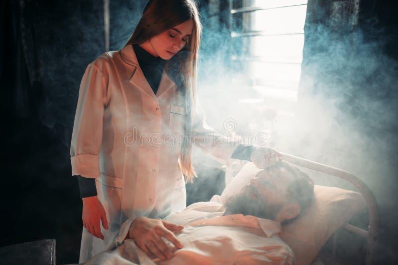 Épouse s'asseyant contre le mari malade dans le lit d'hôpital photos libres de droits