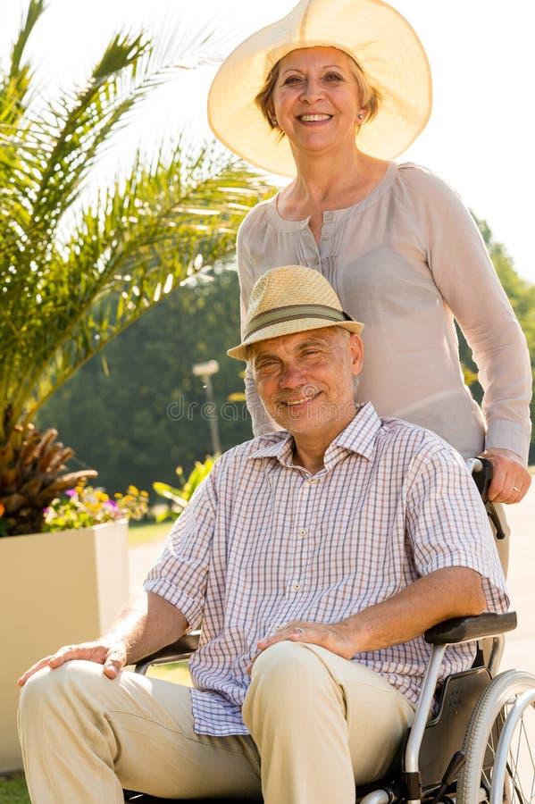 Épouse supérieure avec le mari dans le fauteuil roulant photos stock