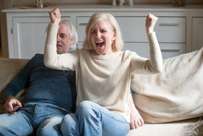 Épouse supérieure enthousiaste encourageant l'équipe de sports préférée à la maison images stock