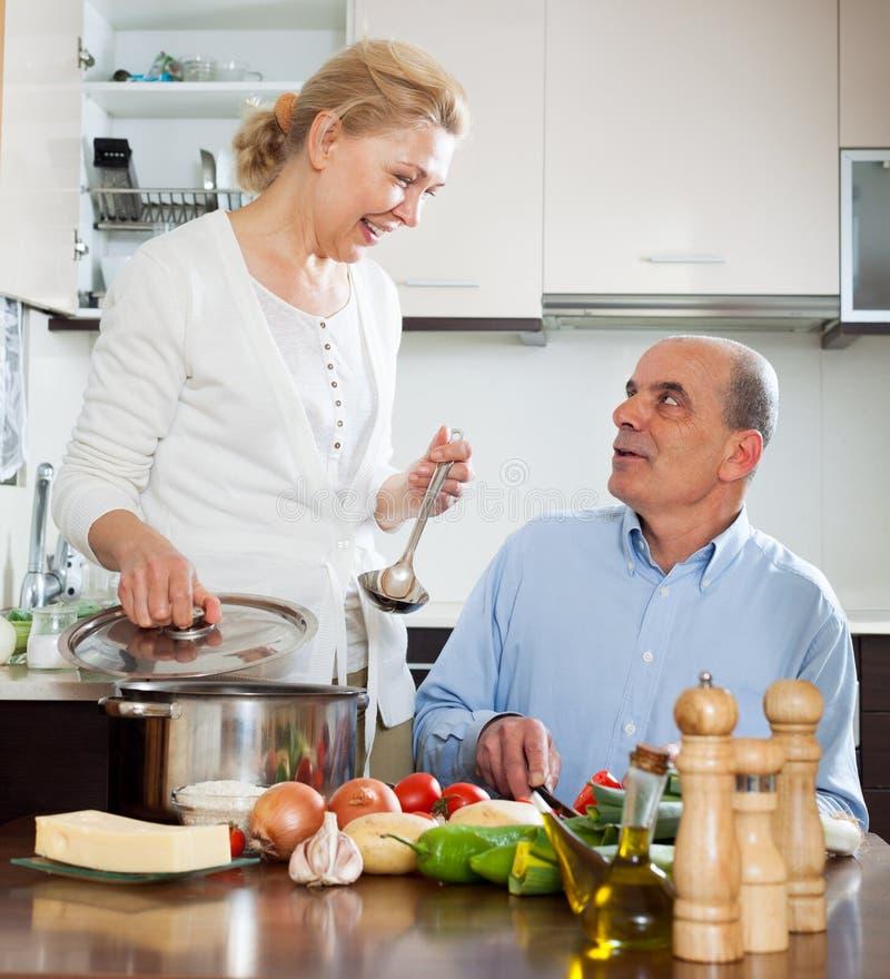 Épouse supérieure et mûre pluse âgé affectueuse faisant cuire ensemble photographie stock libre de droits