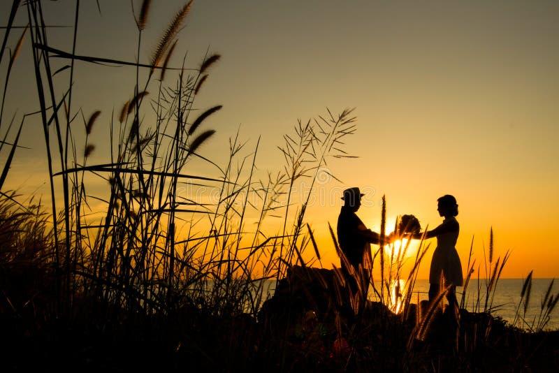 Épouser dans le coucher du soleil image stock