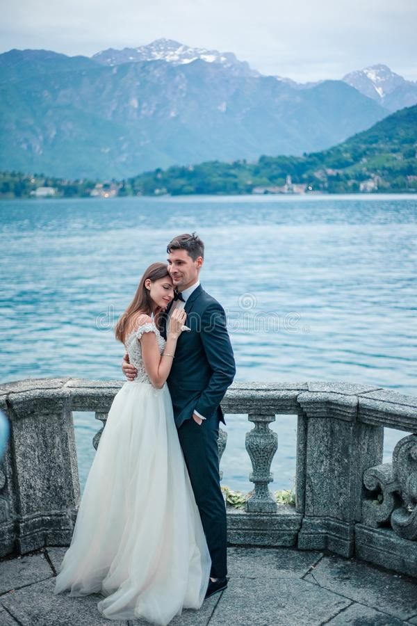 épouser des couples étreignant contre le contexte du lac et des montagnes photos libres de droits