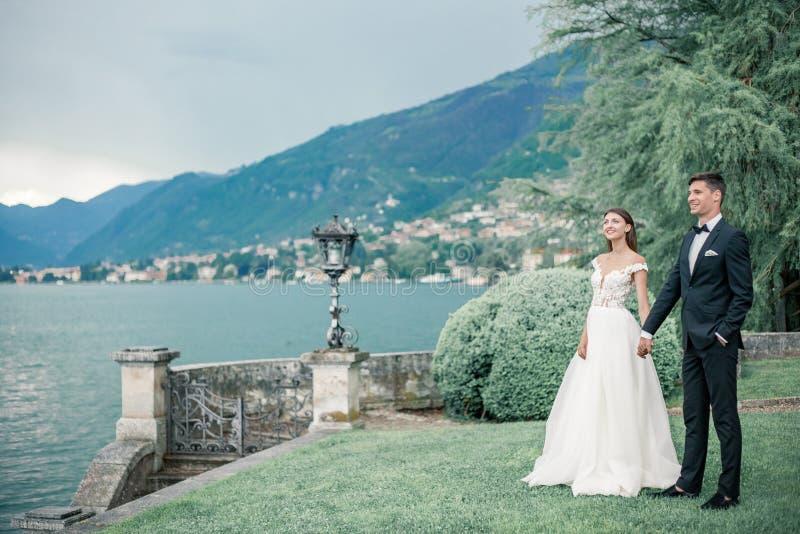 épouser des couples dans la perspective du lac et des montagnes photo libre de droits