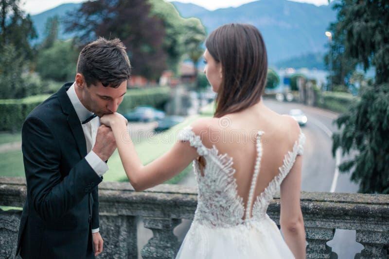 Épouser des couples embrassant sur le fond du lac et des montagnes photographie stock