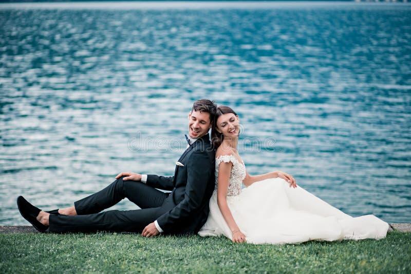Épouser des couples sur le fond du lac et les montagnes le soir photographie stock libre de droits