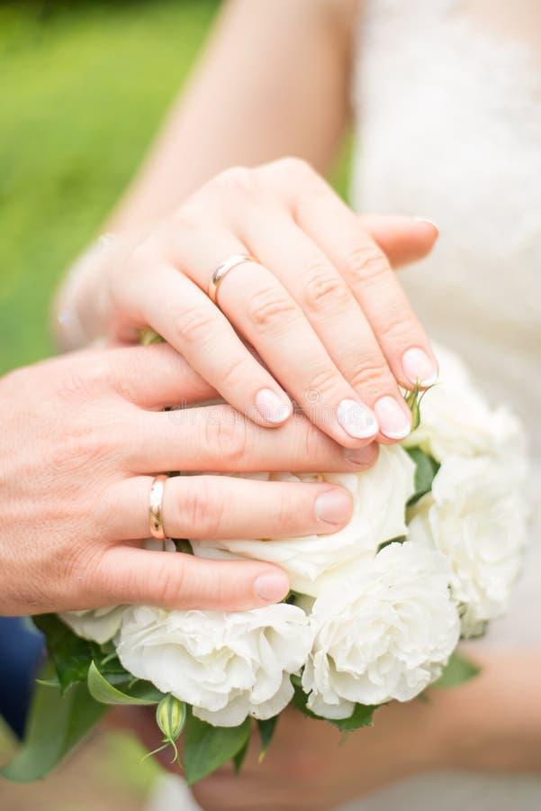 Épouser des mains et des anneaux sur le bouquet de la jeune mariée Déclaration de l'amour Épouser le fond, détails de jour photo libre de droits