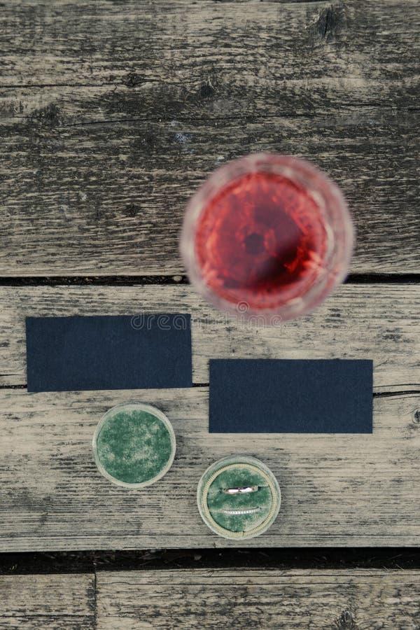 Épouser la configuration d'appartement Carte noire pour des noms Anneaux et verre de vin rose sur le floot en bois gris Fin vers  photo stock