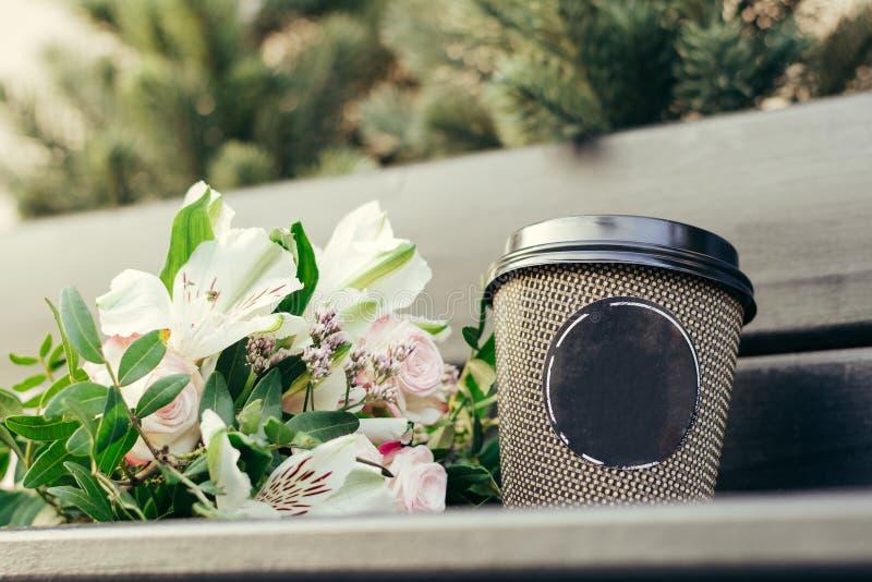 Épouser le bouquet des fleurs avec une tasse image stock
