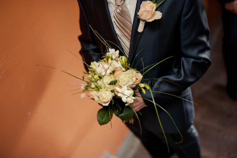 Épouser le marié avec le bouquet de jeunes mariées des fleurs photographie stock libre de droits