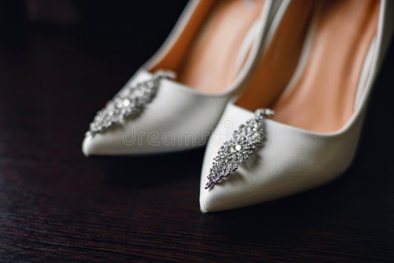 Épouser les chaussures blanches de jeune mariée avec les boucles d'oreille argentées image stock