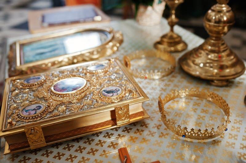 Épouser les couronnes d'or avec l'évangile sur l'église à la cérémonie de mariage photos stock