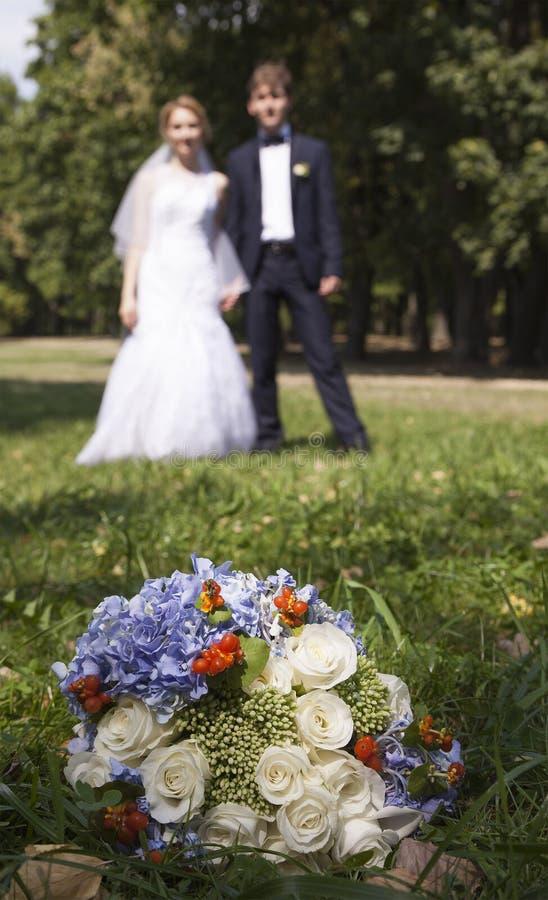 Épousez nouvellement tenir des mains, épousant le bouquet dans le premier plan images libres de droits