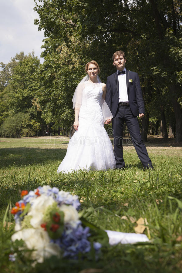 Épousez nouvellement tenir des mains, épousant le bouquet dans le premier plan image libre de droits