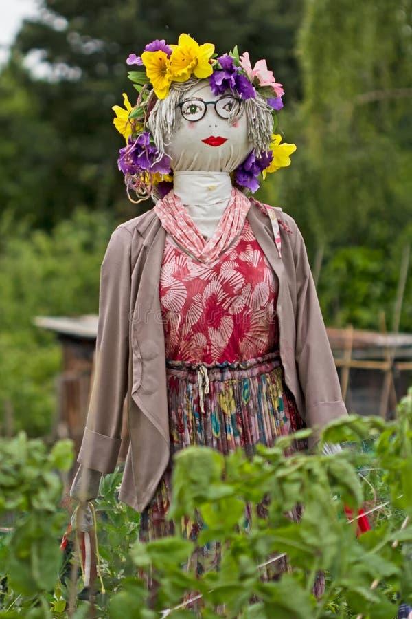 Épouvantail avec les fleurs et la robe rouge photographie stock libre de droits