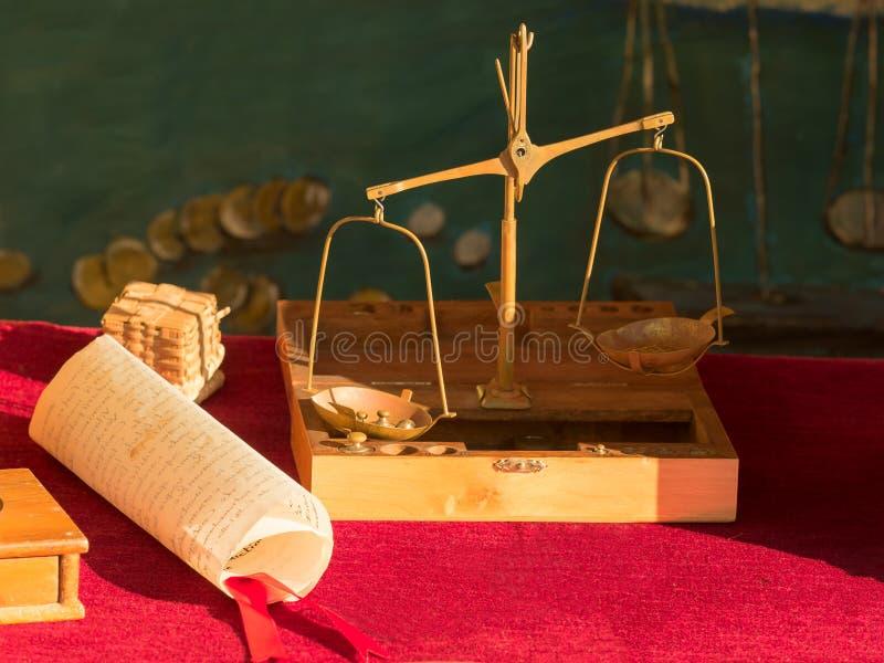 Équilibre antique de balance fait dans le laiton sur la nappe rouge photographie stock libre de droits
