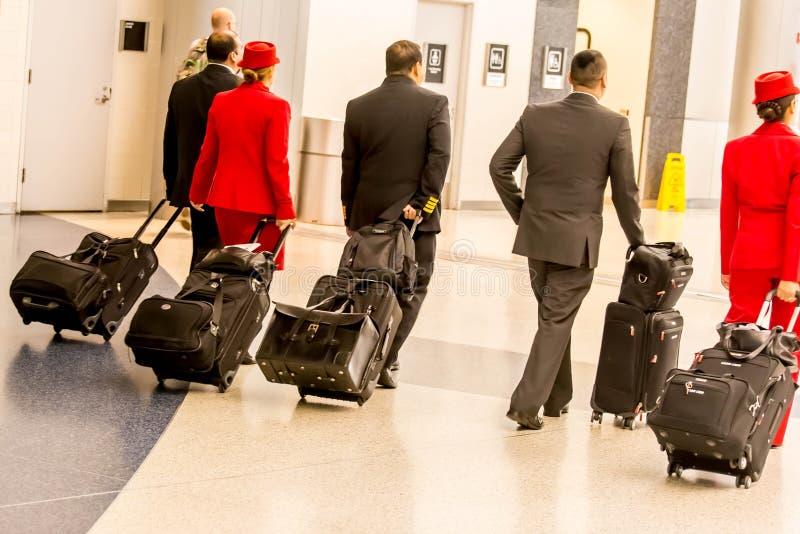 Équipage des aéronefs marchant avec le lugagge dans l'aéroport photo libre de droits