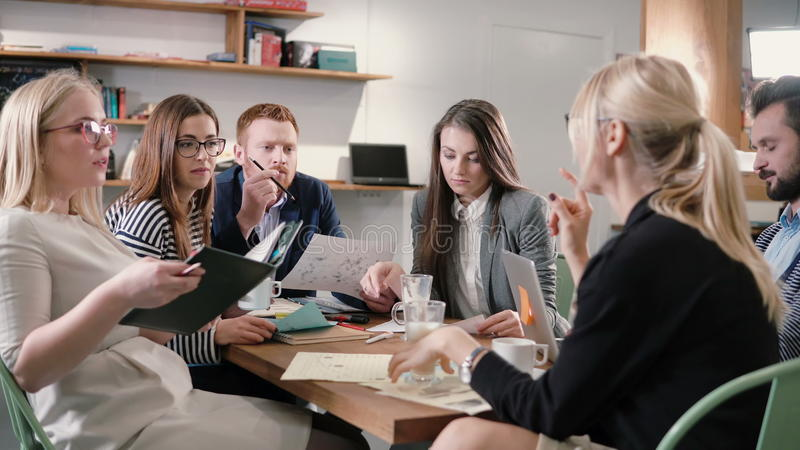 Équipe créative d'affaires à la table dans un bureau de démarrage moderne Le chef féminin explique les détails du projet photos libres de droits