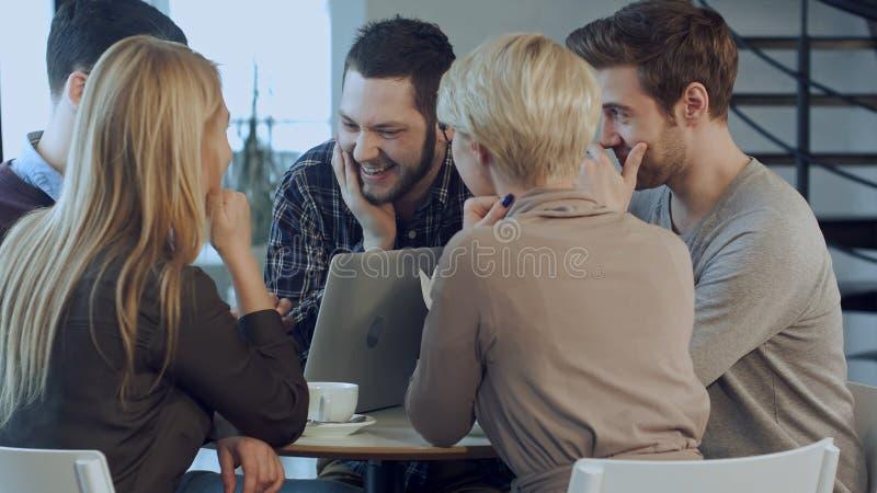 Équipe créative de jeunes concepteurs travaillant ensemble dans leur bureau au cours de la réunion informelle photo stock