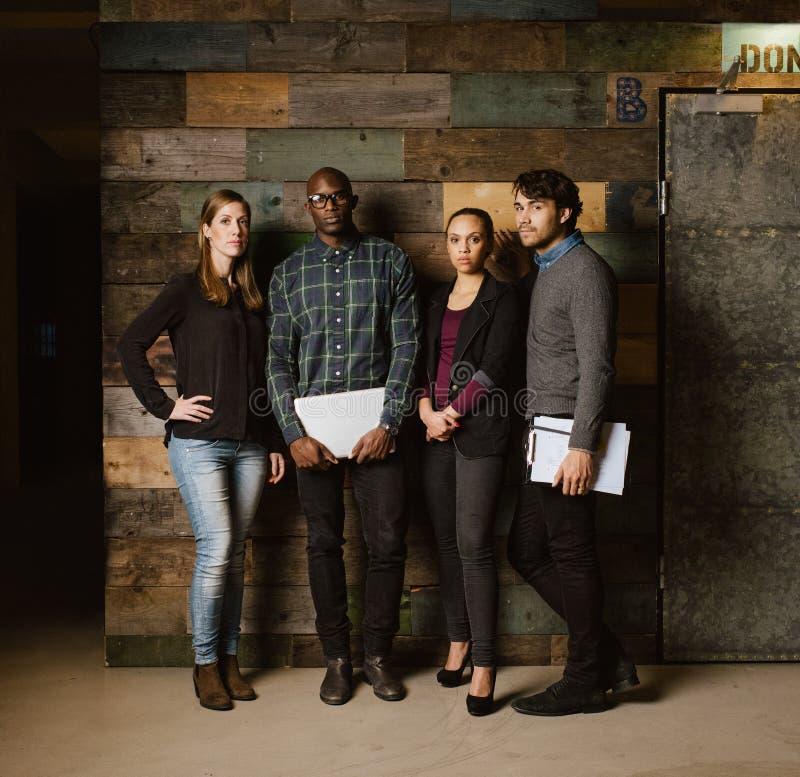 Équipe créative multiraciale posant pour l'appareil-photo dans le bureau image stock