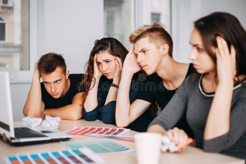 Équipe créative s'asseyant ensemble n'ayant aucune idée photo stock