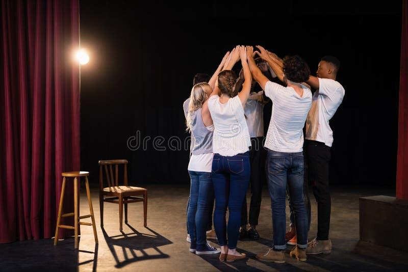 Équipe d'acteurs formant leurs mains empilées images libres de droits