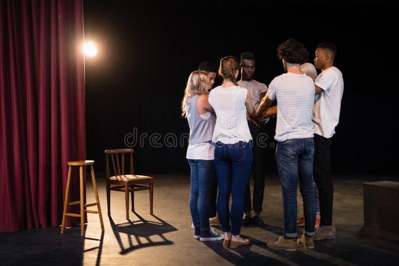 Équipe d'acteurs formant leurs mains empilées image stock