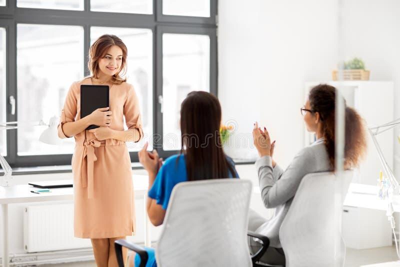 Équipe d'affaires applaudissant à la femme au bureau photos stock
