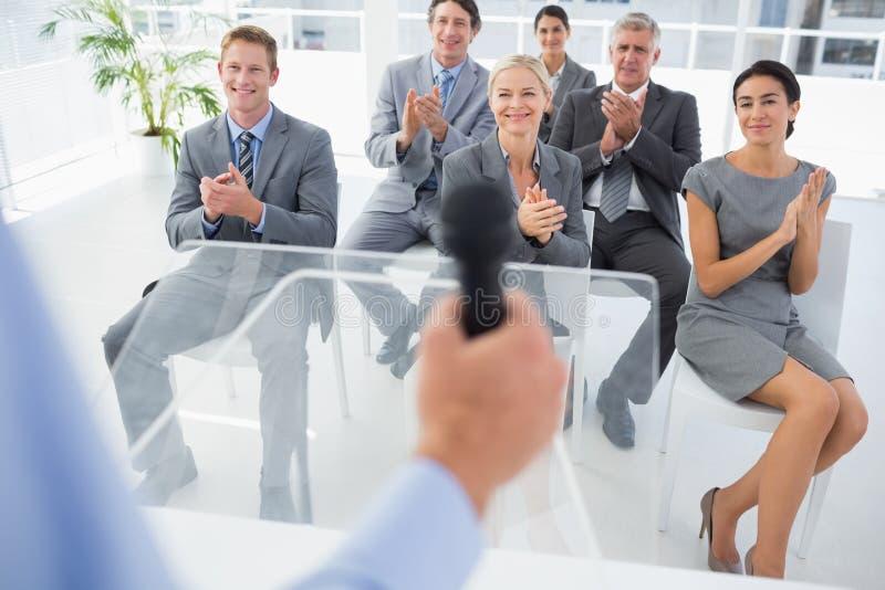Équipe d'affaires applaudissant pendant la conférence photo stock