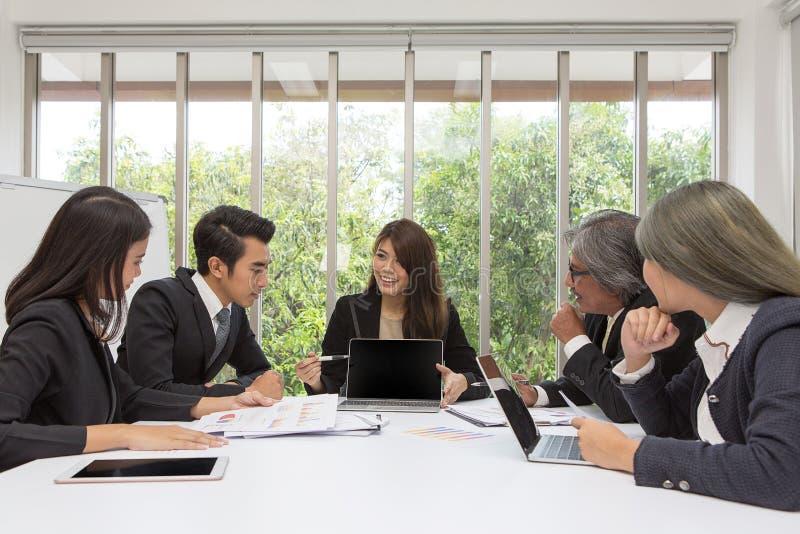 Équipe d'affaires asiatiques posant dans le lieu de réunion Séance de réflexion fonctionnante sur la table dans une chambre Gens  images libres de droits