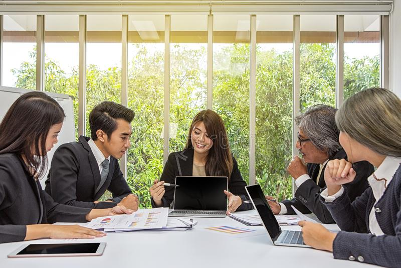 Équipe d'affaires asiatiques posant dans le lieu de réunion Séance de réflexion fonctionnante sur la table dans une chambre Gens  photographie stock