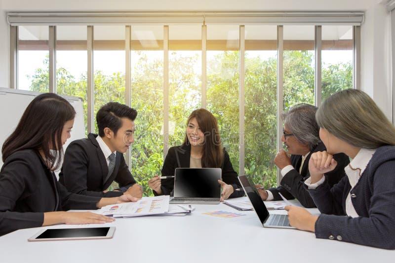 Équipe d'affaires asiatiques posant dans le lieu de réunion Séance de réflexion fonctionnante sur la table dans une chambre Gens  photos libres de droits
