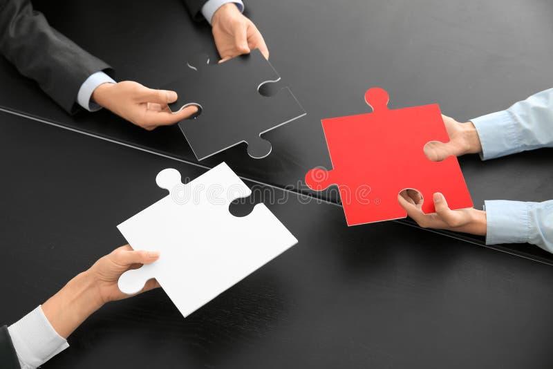 Équipe d'affaires avec des morceaux de puzzle sur la table foncée image libre de droits