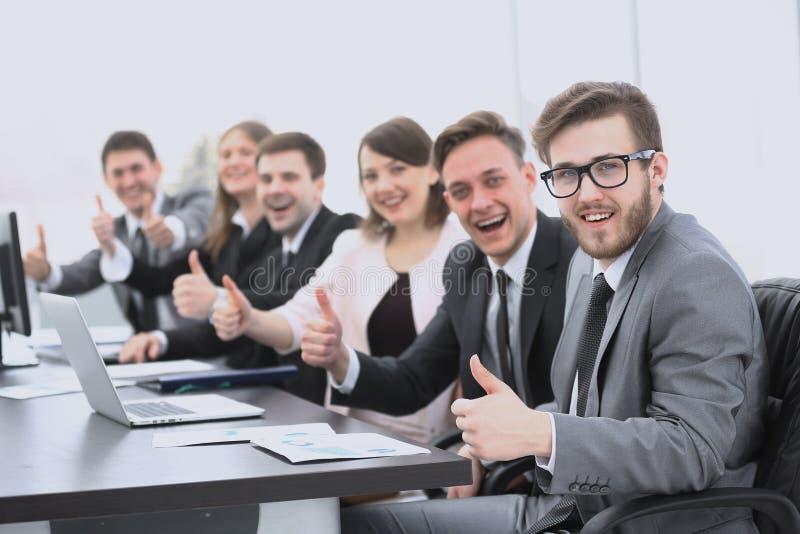 Équipe d'affaires avec des pouces tout en se reposant à son bureau image stock