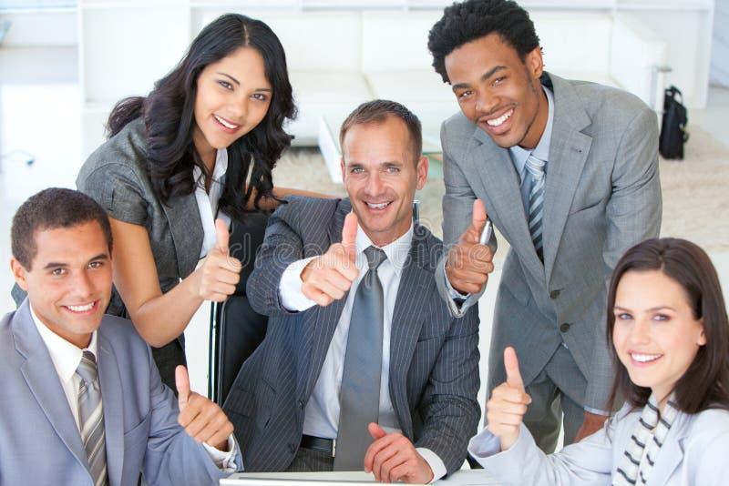 Équipe d'affaires avec des pouces vers le haut dans le bureau photographie stock