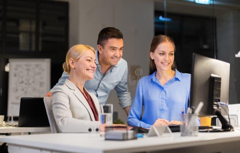 Équipe d'affaires avec l'ordinateur fonctionnant tard au bureau photos stock