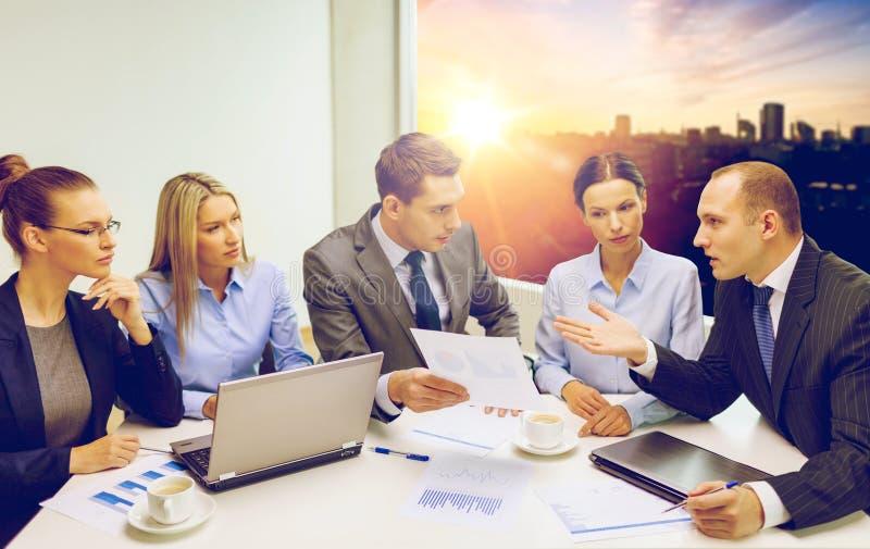 Équipe d'affaires avec l'ordinateur portable ayant la discussion photos stock