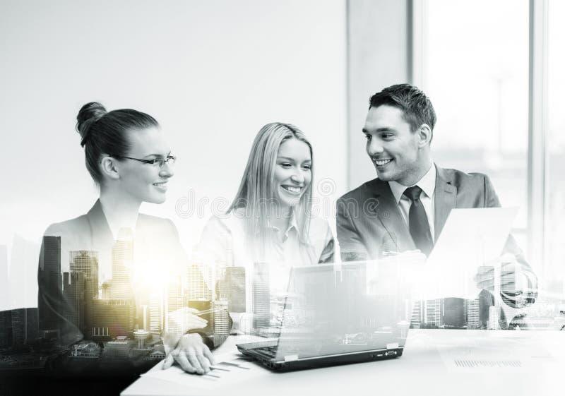 Équipe d'affaires avec l'ordinateur portable ayant la réunion au bureau image libre de droits