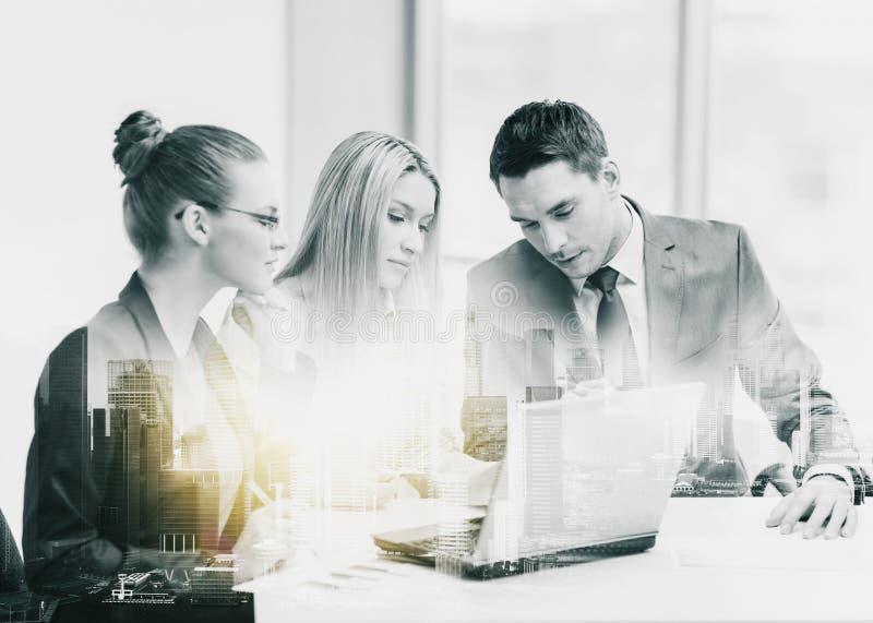 Équipe d'affaires avec l'ordinateur portable ayant la réunion au bureau images stock