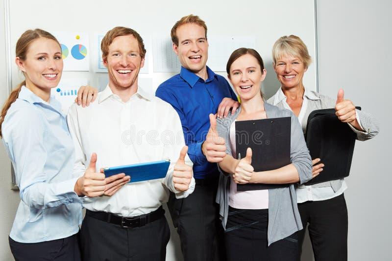 Équipe d'affaires dans le bureau tenant des pouces  images stock