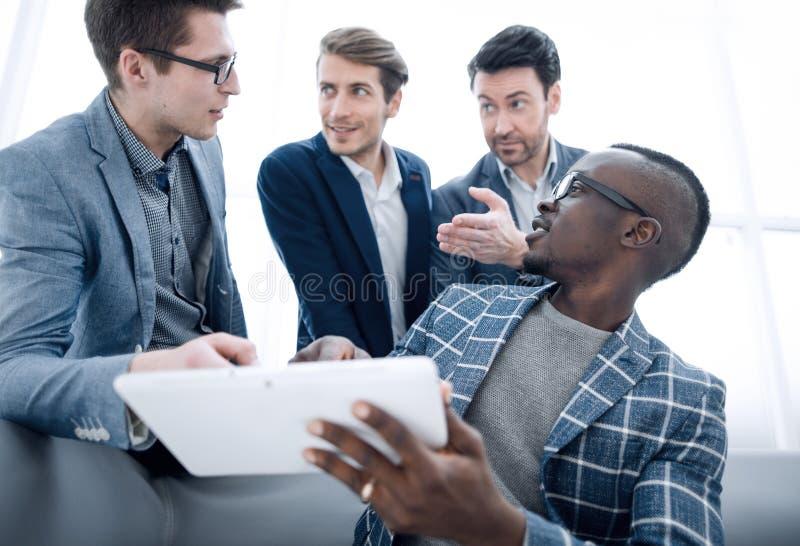 Équipe d'affaires discutant la documentation en ligne photographie stock